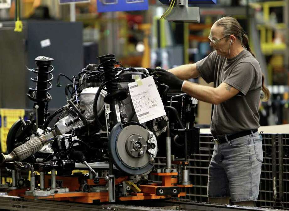 PAUL SANCYA: ASSOCIATED PRESS ECONOMY IN HIGHER GEAR: A line worker earlier this month assembles an engine for a Ford Focus at the Ford Michigan Assembly plant in Wayne, Mich. The number of people applying for jobless benefits dropped to its lowest level since April 2008. Photo: Paul Sancya / AP
