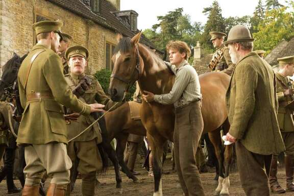 """Captain Nicholls (Tom Hiddleston, far left) and Sergeant Perkins (Geoff Bell) prepare to take Joey away with them. Albert (Jeremy Irvine, center) holds on to Joey defiantly while his father (Peter Mullan, right) looks on in this scene from DreamWorks Pictures' """"War Horse"""". Director Steven Spielberg's epic adventure is set against a sweeping canvas of rural England and Europe during the First World War. Ph: Andrew Cooper/DreamWorks II Distribution Co., LLC."""