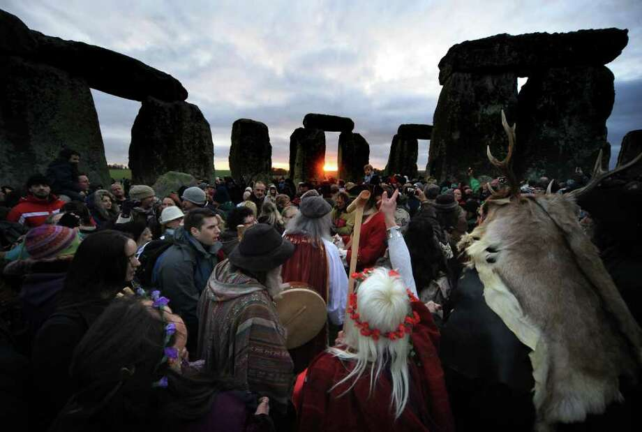 Druids, pagans and revellers cheer as the sun rises at Stonehenge on December 22, 2011 in Wiltshire, England. The unseasonable warm weather encouraged a larger than normal crowd to gather at the famous historic stone circle to celebrate the sunrise closest to the Winter Solstice, the shortest day of the year. Photo: Matt Cardy, Getty / 2011 Getty Images