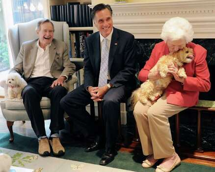 Republican presidential candidate, former Massachusetts Gov. Mitt Romney, center, visits with former President George H.W. Bush, his wife Barbara and their dogs Mimi and Bibi, Thursday, Dec. 1, 2011, at their home in Houston. Photo: AP