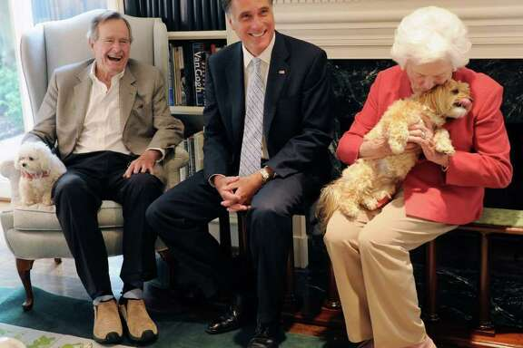 Republican presidential candidate, former Massachusetts Gov. Mitt Romney, center, visits with former President George H.W. Bush, his wife Barbara and their dogs Mimi and Bibi, Thursday, Dec. 1, 2011, at their home in Houston.