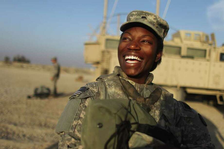 Spc. Shunterika Lewis from the 3rd Brigade, 1st Cavalry Division, laughs while preparing to depart in the last convoy from Iraq last Saturday at Camp Adder, near Nasiriyah. Photo: MARIO TAMA, ASSOCIATED PRESS