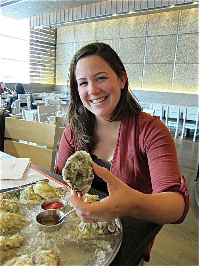 Alison Cook : staff AUTHOR: Shucked writer Erin Byers Murray holds an oyster at the Island Creek Oyster Bar in Boston. Photo: Alison Cook