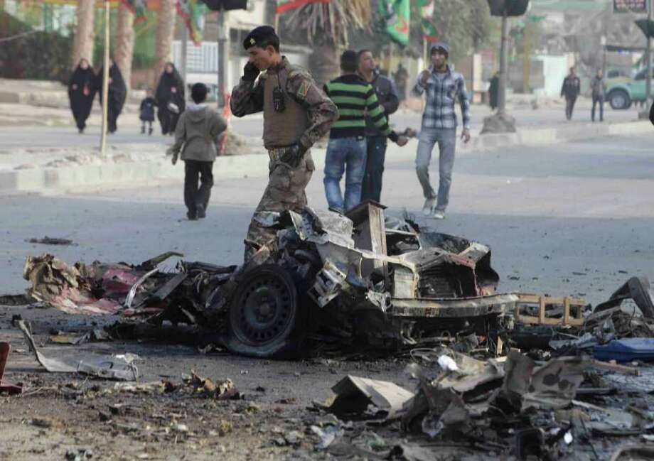 People gather at the scene of a car bomb attack in Baghdad, Iraq, Thursday, Dec. 22, 2011. A wave of bombings ripped across Baghdad on Thursday morning. Photo: Karim Kadim, Associated Press / AP