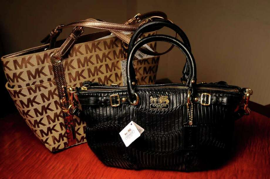 Dave Rossman : For the Chronicle MANY GRAB BAGS: Handbags from Michael Kors and Coach are hot sellers at the Macy's at Memorial City Mall. Photo: Dave Rossman / © 2011 Dave Rossman