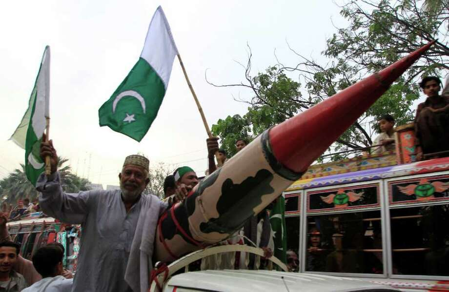 SHAKIL ADIL : ASSOCIATED PRESS  STILL AT ODDS: A supporter of Pakistan's ruling party stands by a model of a mock missile at a rally to condemn NATO strikes on Pakistani troops, in Karachi, Pakistan. Photo: Shakil Adil / AP