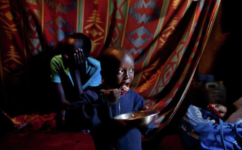 MEAGER PORTION: Joel Abongo, 6, eats rice and beans in the shack of his mother, Mary, left, and father, Ishmael, all of whom are HIV-positive, in a Nairob slum. If Ishmael has no food to eat in the morning, he's too weak to travel to seek work as a house painter. Photo: Ben Curtis / AP