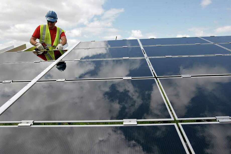 Jared  Anderson works on a panel at a CPS Energy solar farm off Blue Wing Road on the South Side. The  solar plant includes 214,500  panels and covers 110 acres. Solar and wind  are two sources  of green  energy used by CPS. Photo: JERRY LARA, San Antonio Express-News / glara@express-news.net