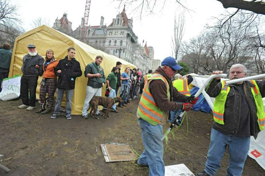 Occupy Albany members form a human chain around the last tent in Academy Park as DGS workers take down tents on Thursday, Dec. 22, 2011 in Albany, N.Y. Moments later the members pulled up the tent and marched around Albany with it. (Lori Van Buren / Times Union) Photo: Lori Van Buren