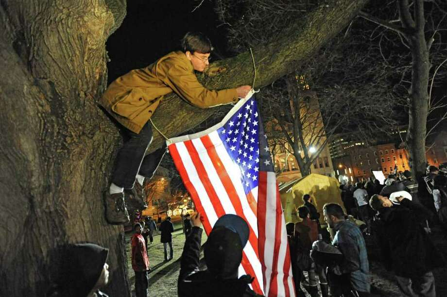 Occupy Albany member Zach Caron-Noble, 19, of Poestenkill climbs a tree to hang the American Flag after marching through Albany with the last tent from Academy Park on Thursday, Dec. 22, 2011 in Albany, N.Y.  (Lori Van Buren / Times Union) Photo: Lori Van Buren
