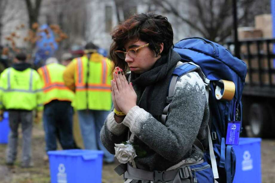 Occupy Albany member Elena Cruzallen of Albany prays as DGS workers take down the last tents in Academy Park on Thursday, Dec. 22, 2011 in Albany, N.Y.  (Lori Van Buren / Times Union) Photo: Lori Van Buren