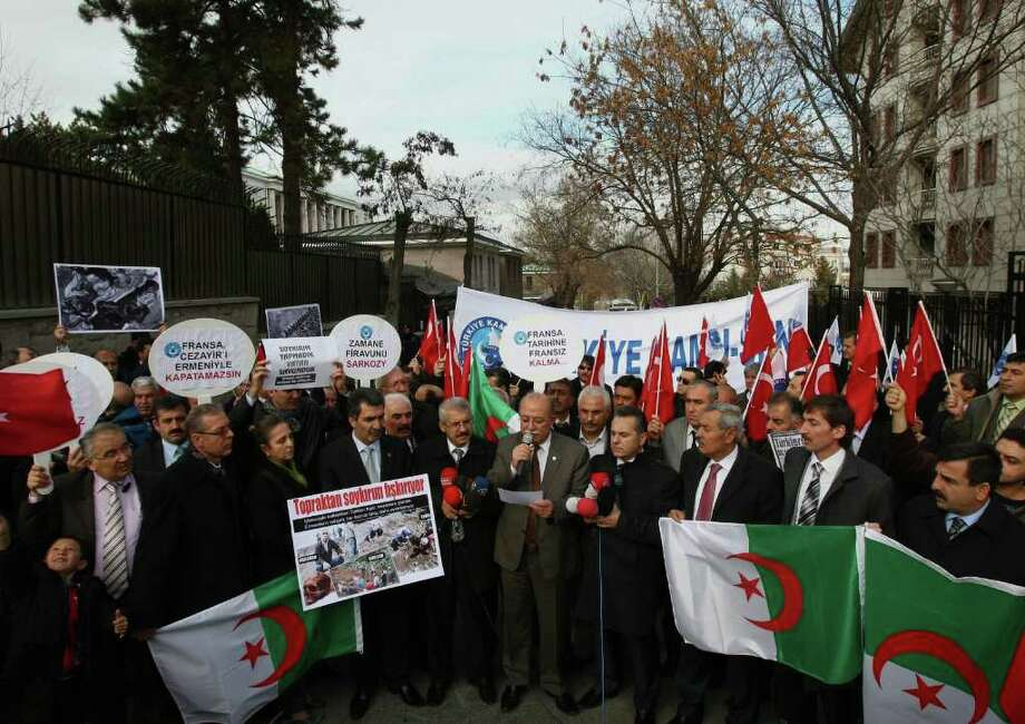 Members of a Turkish union hold Turkish and Algerian flags as they protest against France outside the French Embassy in Ankara, Turkey, Thursday, Dec. 22, 2011. French lawmakers are to vote on a measure that would make it a crime in France to deny that the mass killings of Armenians in 1915 amounted to a genocide, a measure that could put France on a collision course with Turkey, a strategic ally. Turkey wants the killings left to historians and has lashed out at France, warning that it will withdraw its ambassador if the measure becomes law.(AP Photo/Burhan Ozbilici) Photo: Burhan Ozbilici                  / AP