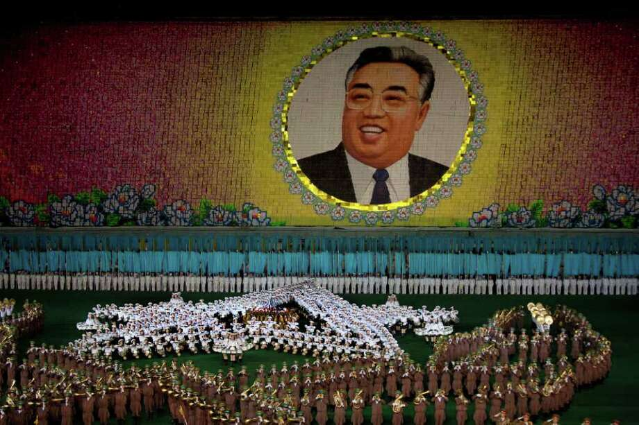 A portrait of the late North Korean leader Kim Il Sung is made by people holding up colored cards at a stadium during an Arirang festival performance in Pyongyang on Aug. 24. The tools for making the myth have been developed over two generations, dating back to Kim's father, late President Kim Il Sung.  (AP Photo/David Guttenfelder) Photo: David Guttenfelder / AP