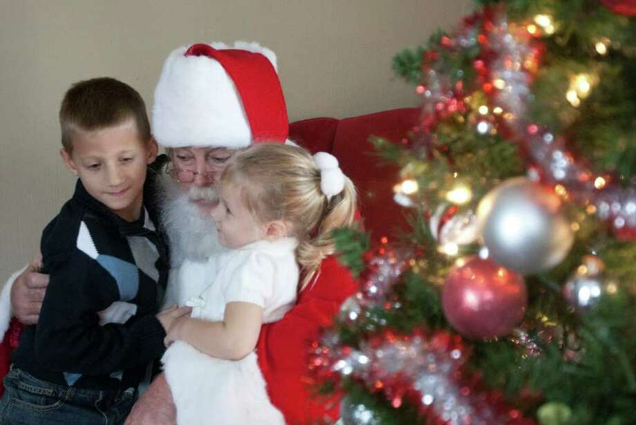 For 28 years, Kingwood resident Deryl McKenzie has been known as Santa Claus, McKenzie is shown with 6-year-old Nathan Johnson and his 2-year-old sister, Kara, in Humble.  ( James Nielsen / Chronicle ) Photo: James Nielsen / © 2011 Houston Chronicle