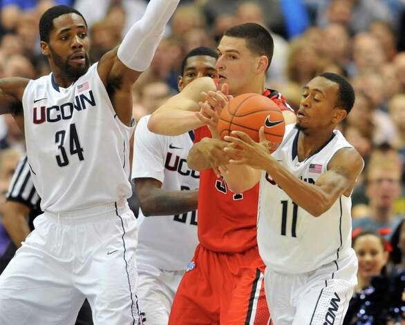 Connecticut's Ryan Boatright (11) steals the ball from Fairfield's Ryan Olander, center, as Connecticut's Alex Oriakhi (34) defends in the first half of an NCAA college basketball game in Hartford, Conn., Thursday, Dec. 22, 2011.  (AP Photo/Jessica Hill) Photo: Jessica Hill/Associated Press / AP2011
