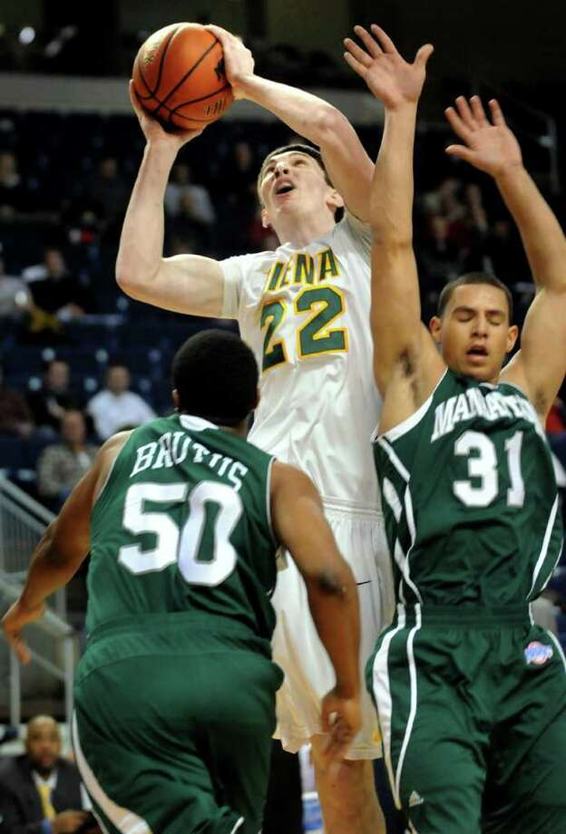 Siena's Ryan Rossiter (22), center, shoots for the hoop as Manhattan's Kidani Brutus (50), left and Michael Alvarado (31) defend during their basketball game at the MAAC Championships on Friday, March 4, 2011, at Webster Band Arena at Harbor Yard in Bridgeport, Conn. (Cindy Schultz / Times Union) Photo: Cindy Schultz