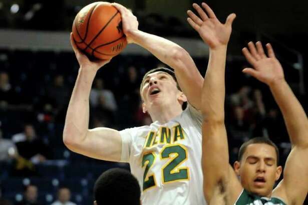 Siena's Ryan Rossiter (22), center, shoots for the hoop as Manhattan's Kidani Brutus (50), left and Michael Alvarado (31) defend during their basketball game at the MAAC Championships on Friday, March 4, 2011, at Webster Band Arena at Harbor Yard in Bridgeport, Conn. (Cindy Schultz / Times Union)