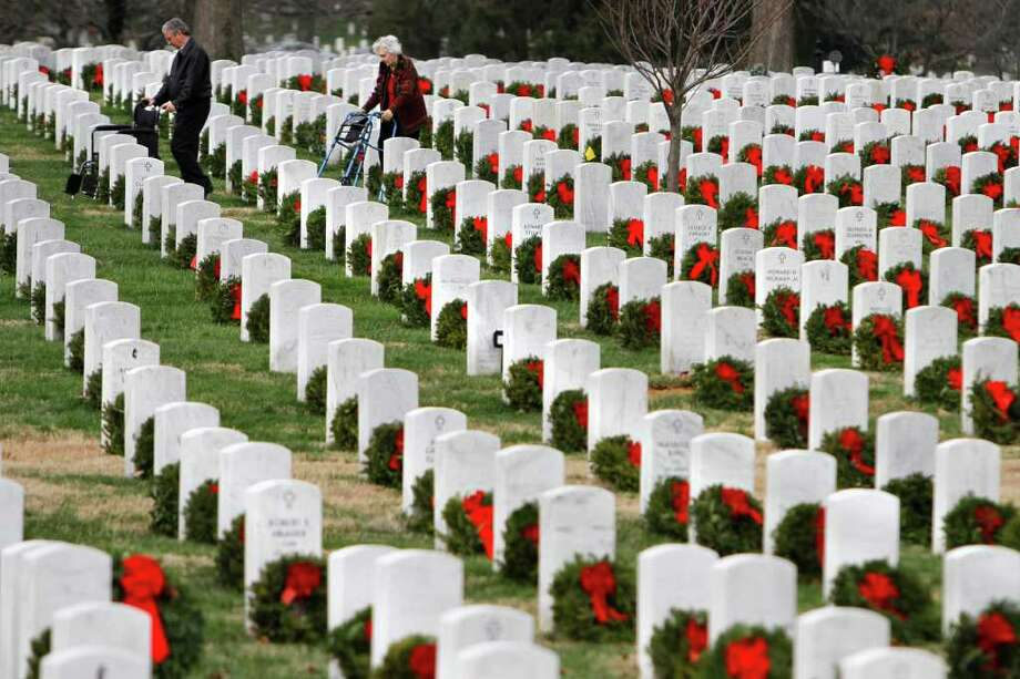JACQUELYN MARTIN : ASSOCIATED PRESS  PAYING HOMAGE: People walk among gravestones adorned with Christmas wreaths in Section 60 of Arlington National Cemetery on Friday, a day after the Pentagon declared an end to the Iraq war. Section 60 is where many of those who died in Iraq and Afghanistan are buried. Photo: Jacquelyn Martin / AP