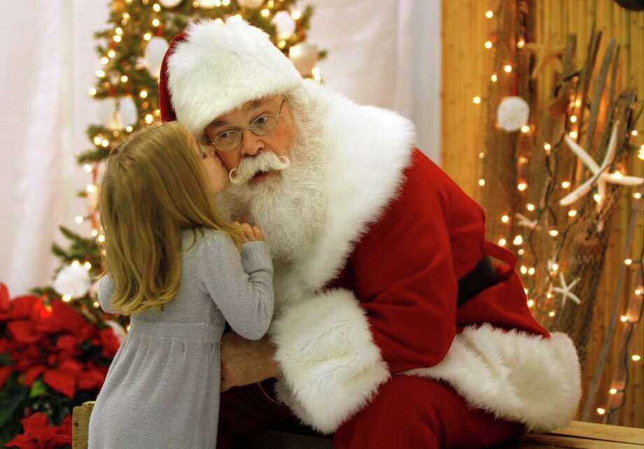 """TOM COPELAND : ASSOCIATED PRESS  PERK ON THE CHEEK: Cliff Snider, who's filled in for Santa since he was a teenager, gets a reward after hearing 3-year-old Bella Champion's Christmas wishes recently in Emerald Isle, N.C. Santas are taught to answer big-ticket requests with: """"There's a lot of children asking for that. What else do you want?"""" Snider, 64, says he has to use it less and less these days, however. Photo: Tom Copeland / FR170645 AP"""