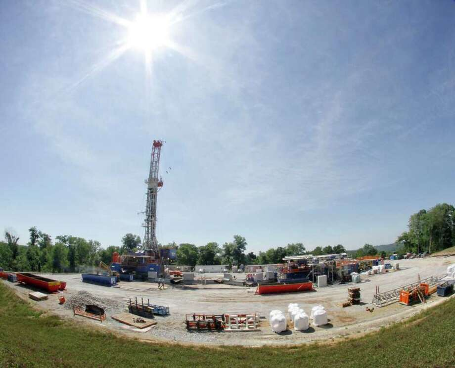 "In this July 27, 2011 photo, the sun shines over a Range Resources well site in Washington, Pa. The company is  one of many drilling into the Marcellus Shale layer deep underground and ""fracking"" the area to release natural gas. (AP Photo/Keith Srakocic) Photo: Keith Srakocic / AP"