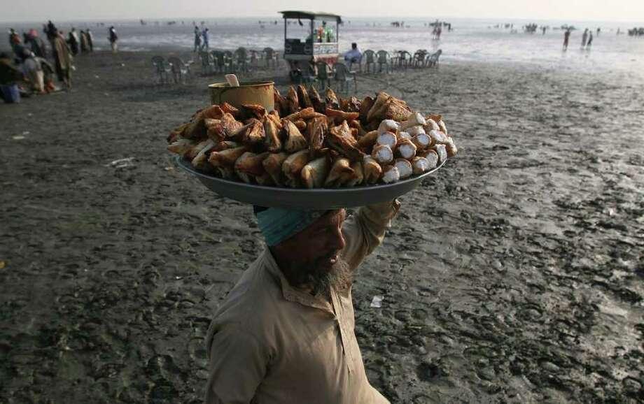 A Pakistani snack seller waits for customers at Clifton beach in Karachi, Pakistan on Thursday, Dec. 22, 2011. (AP Photo/Fareed Khan) Photo: Fareed Khan / AP