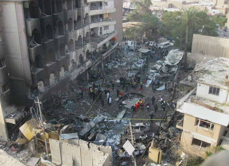Iraqi security forces gather the scene of a car bomb attack in Baghdad, Iraq, Thursday, Dec. 22, 2011. A wave of bombings ripped across Baghdad on Thursday morning killing and wounding hundreds of people, Iraqi officials said, in the worst violence Iraq has seen for months. The bloodbath comes just days after American forces left the country. (AP Photo/Hadi Mizban) Photo: Hadi Mizban / AP