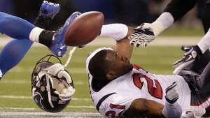 Houston Texans defensive back Brice McCain (21) loses his helmet after breaking up a pass intended for Indianapolis Colts wide receiver Austin Collie during the second quarter of an NFL football game at Lucas Oil Stadium Thursday, Dec. 22, 2011, in Indianapolis.