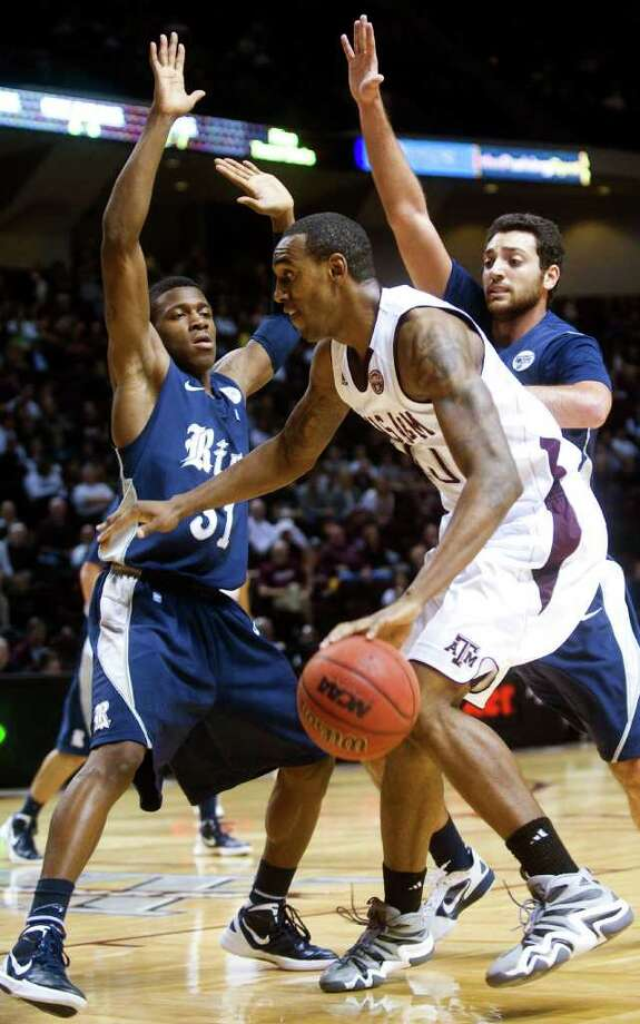 Texas A&M's David Loubeau, center, looks for room between Rice's Dylan Ennis, left, and Ahmad Ibrahim during the first half of an NCAA college basketball game, Thursday, Dec. 22, 2011, in College Station, Texas. (AP Photo/Bryan-College Station Eagle, Stuart Villanueva) Photo: Stuart Villanueva, Associated Press / Bryan-College Station Eagle