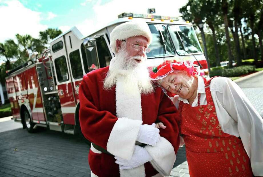 Beverly Bennis, 87, a resident of Brookdale Senior Living Center in suburban West Palm Beach, is greeted by a man dressed as Santa Claus before taking a ride in a Palm Beach Fire Rescue fire truck in West Palm Beach, Fla., Wednesday, Dec. 21, 2011. Bennis had her wish fulfilled by Jeremy Bloom's Wish of a Lifetime, a non-profit organization that grants wishes to senior citizens across the U.S. Photo: Richard Graulich, Associated Press / Palm Beach Post