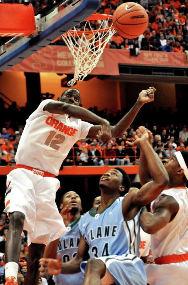 Syracuse's Baye Keita (12) blocks a shot by Tulane's Trevante Dyre (34) during the first half of an NCAA college basketball game in Syracuse, N.Y., Thursday, Dec. 22, 2011. (AP Photo/Kevin Rivoli) Photo: Kevin Rivoli