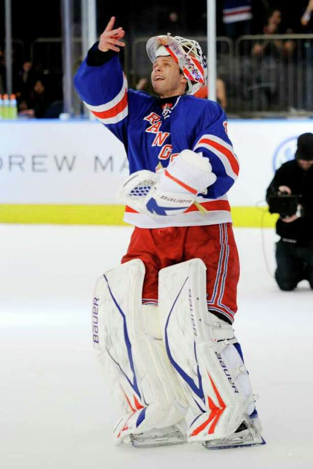 New York Rangers goalie Martin Biron throws a puck into the crowd after making 24 saves in the Rangers' 4-2 win over the New York Islanders in an NHL hockey game at New York's Madison Square Garden, Thursday, Dec. 22, 2011. (AP Photo/Henny Ray Abrams) Photo: Henny Ray Abrams