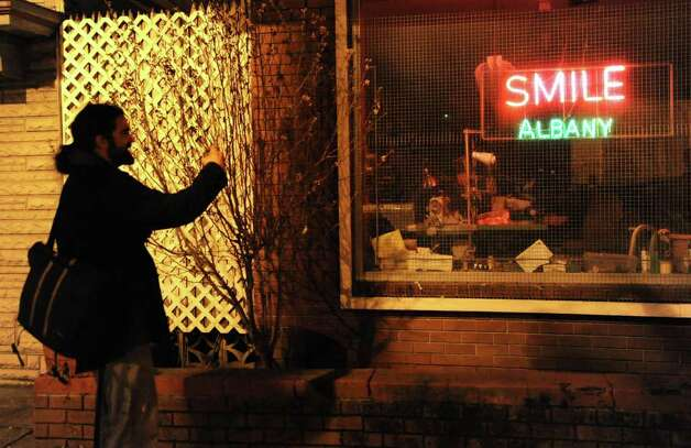 An Occupy Albany member stops to take a photo of a sign in a window as the movement marches through Albany with the last tent from Academy Park on Thursday, Dec. 22, 2011 in Albany, N.Y.  (Lori Van Buren / Times Union) Photo: Lori Van Buren