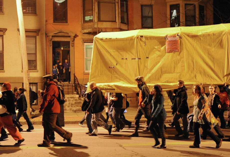 People watch from their front stoop as Occupy Albany members march through Albany with the last tent from Academy Park on Thursday, Dec. 22, 2011 in Albany, N.Y.  (Lori Van Buren / Times Union) Photo: Lori Van Buren
