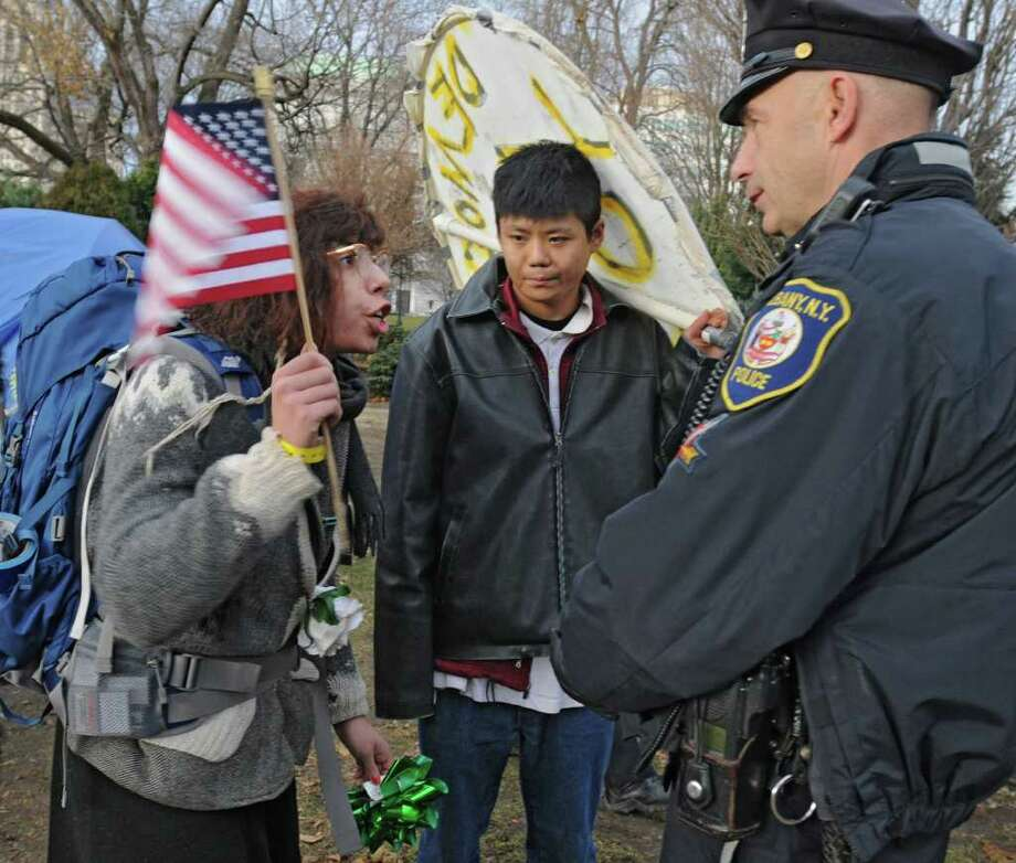Occupy Albany member Elena Cruzallen of Albany yells at Albany police officer Bill Wilson as DGS workers take down the last tents in Academy Park on Thursday, Dec. 22, 2011 in Albany, N.Y.  Kevin Cheng of Ellenville, middle looks on.(Lori Van Buren / Times Union) Photo: Lori Van Buren