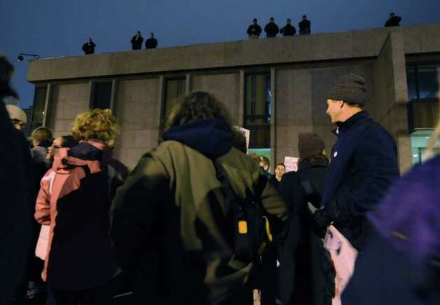 Occupy Albany protesters gathered outside Albany City Court Thursday night  in Albany N.Y., Dec. 22, 2011. A group, which appeared to be Albany Police, monitored the protesters from the City Court roof. (Will Waldron / Times Union) Photo: Will Waldron
