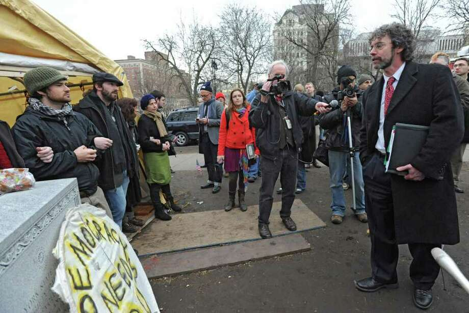 Attorney Mark Mishler, right, leads the chants with Occupy Albany members as DGS workers take down the last tents in Academy Park on Thursday, Dec. 22, 2011 in Albany, N.Y.  (Lori Van Buren / Times Union) Photo: Lori Van Buren