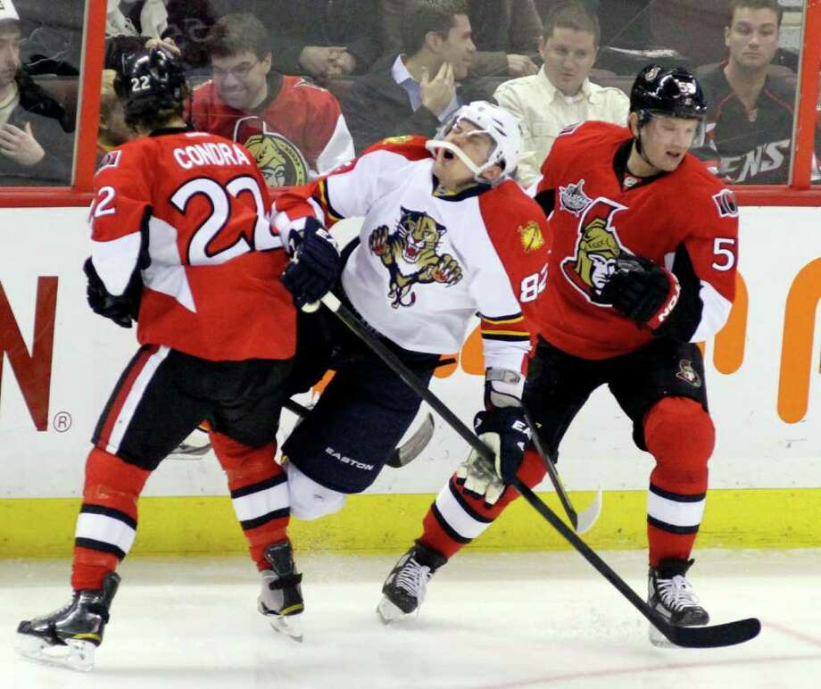 FRED CHARTRAND: ASSOCIATED PRESS CRUNCH TIME: The Panthers' Tomas Kopecky, right, feels the effects of a hit from the Senators' Erik Condra. Photo: Fred Chartrand / CP