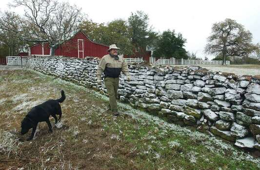 Sam Golden walks with his dog Shooter along a snow-blasted rock wall on his ranch north of Fredericksburg in the Willow City community in 2001. The Hill Country could get light snowfall Christmas Eve morning thanks to a cold front moving through the area tonight and into Saturday morning. Photo: TOM REEL , SAN ANTONIO EXPRESS-NEWS  / SAN ANTONIO EXPRESS-NEWS