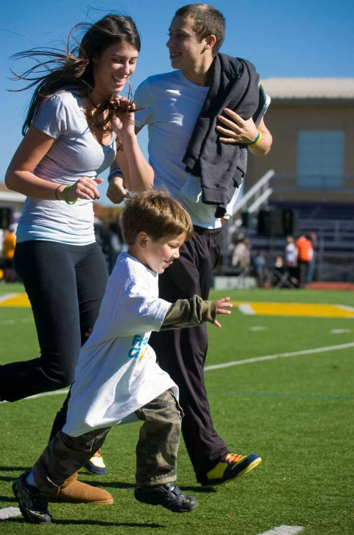 Arthur Burba, 3, runs with Caroline Chaplin, 16, and Matt Low, 17, during the Friendship Circle's Frienship Walk, which raised over $110,000 at Westhill High School in Stamford, Conn. on Sunday, Oct. 25, 2009.