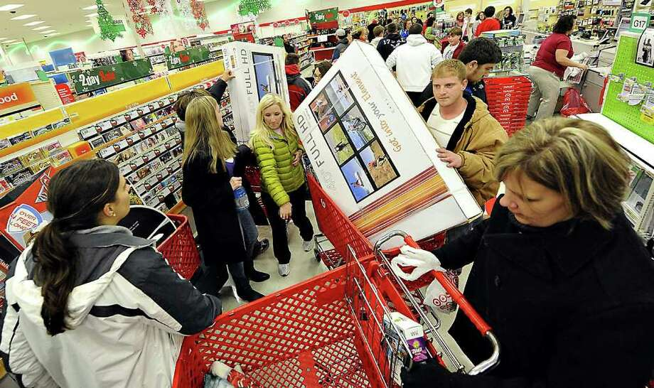 FILE - In this Nov. 25, 2011 file photo, shoppers scramble for door buster deals at Target, in Bowling Green, Ky. U.S. consumers spent at a lackluster rate in November as their incomes barely grew, suggesting that U.S. households may struggle to sustain their spending into 2012.(AP Photo/Daily News, Joe Imel, File) Photo: Joe Imel / AP2011