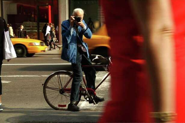 Bill Cunningham takes a photograph on the streets in New York City in the documentary Bill Cunningham New York.