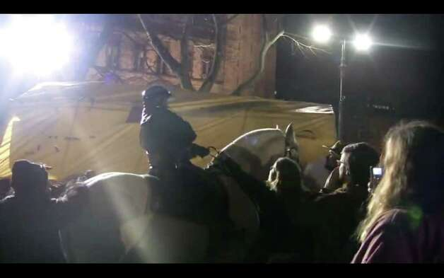 Video frame grab showing the moment when a horse mounted police officer engaged Occupy Albany members with pepper spray during Thursday night?s clash with police. (Marie Anne Sheehan) Photo: Will Waldron