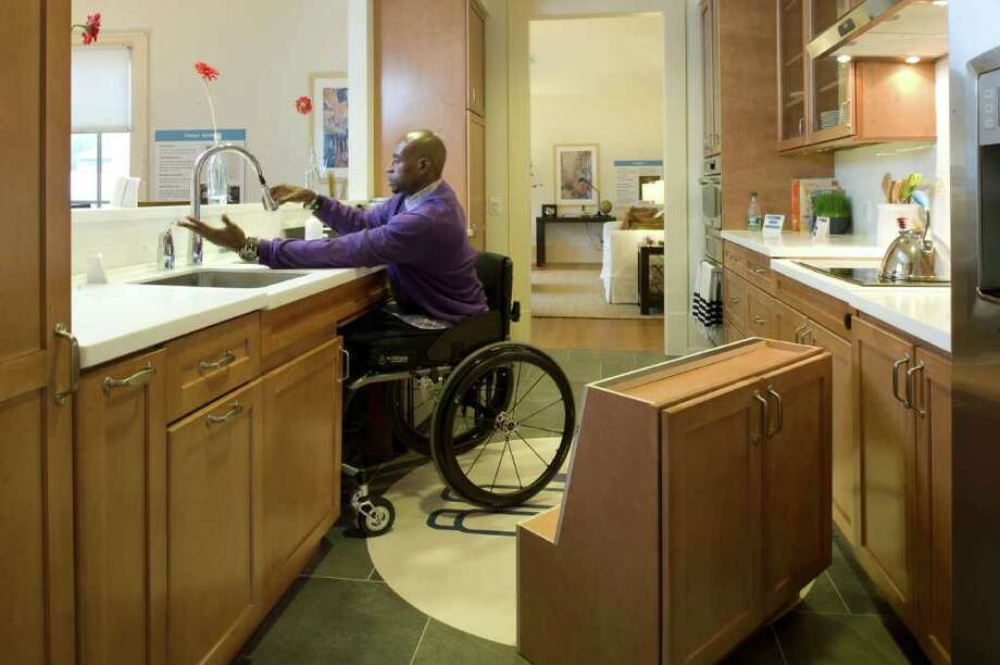 JOHN McDONNELL : WASHINGTON POST MORE THAN ACCESSIBLE: Retired Staff Sgt. Eugene Simpson demonstrates a wheelchair-accessible kitchen sink in one of the homes in Fort Belvoir, Va., that are part of the Wounded Warrior Home Project. The public-private project enlisted architect Michael Graves to create state-of-the-art homes and amenities for wounded soldiers. Photo: John McDonnell, Washington Post / WASHINGTON POST