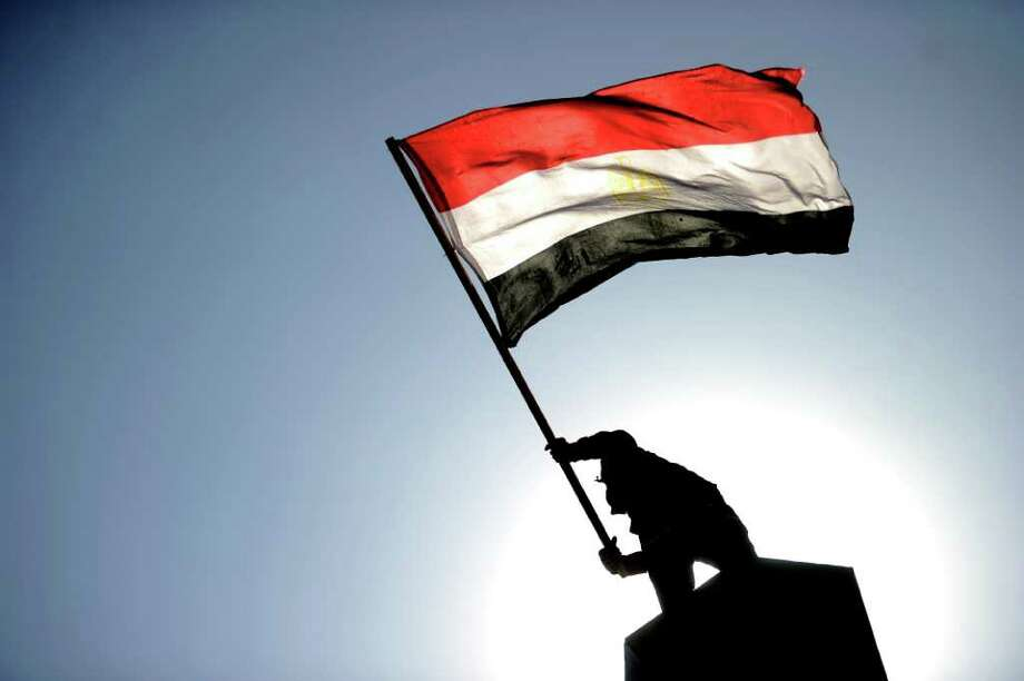 An Egyptian protester waves his national flag atop a structure in Cairo's Tahrir Square on December 23, 2011 during a mass rally against the ruling military, which sparked outrage when its soldiers were taped beating women protesters. AFP PHOTO / FILIPPO MONTEFORTE Photo: FILIPPO MONTEFORTE, Getty / FILIPPO MONTEFORTE