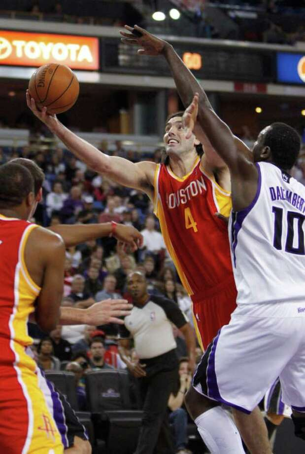 Houston Rockets forward Luis Scola, of Argentina, goes to the basket past Sacramento Kings center Samuel Dalembert, right, during the first quarter of an NBA basketball game in Sacramento, Calif., Monday, March 7, 2011. (AP Photo/Rich Pedroncelli) Photo: Rich Pedroncelli / AP