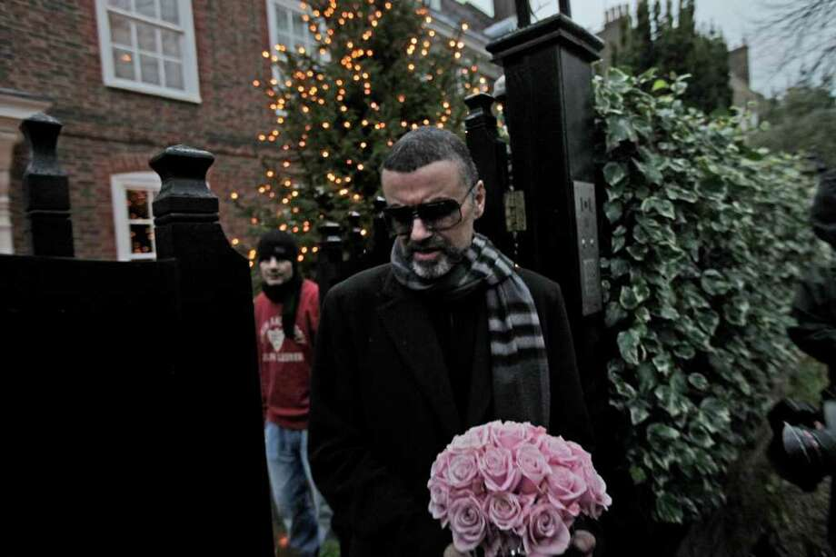 British singer George Michael leaves his house in north London, Friday, Dec. 23, 2011. George Michael, short of breath and appearing weak, said Friday he has recovered from a life-threatening bout with pneumonia that kept him in a Vienna hospital for a month.(AP Photo/Lefteris Pitarakis) Photo: Lefteris Pitarakis / AP