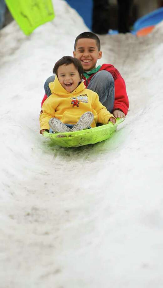 Abraham Cuevas, 11, sleds down a hill of snow with his brother Joshua Cuevas, 2, during Discovery Green's FUNomenal Fridays event with the ice donated by Ice Express, Dec. 23, 2011, in Houston. Photo: Karen Warren, Houston Chronicle / © 2011 Houston Chronicle