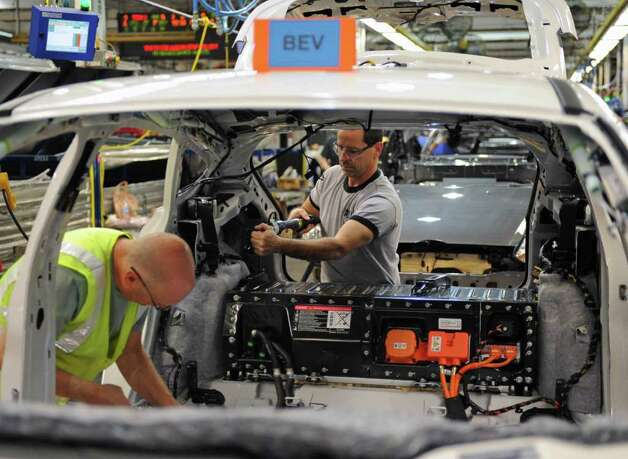 Workers at Ford's Michigan Assembly Plant in Wayne install components in the new Focus battery-electric vehicle as it comes down the assembly line on Dec. 14. The lithium-ion battery pack is clearly visibile between the cargo area and the space for the rear seatback. Photo: Ford Motor Co., Wieck / Ford