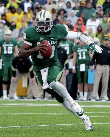 FILE - This Dec. 3, 2011 file photo shows Baylor quarterback Robert Griffin III (10) finding running room behind the line of scrimmage against Texas in the first half of an NCAA college football game in Waco, Texas. Griffin III has won The Associated Press college football player of the year, adding another award to his impressive postseason haul. Photo: AP