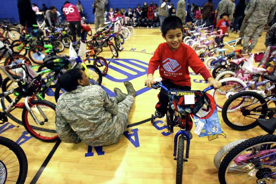 Jonathan Acrophs rides his new bike after reservists from the 433rd Airlift Wing from Lackland Air Force Base donated more than 50 bicycles to the Boys and GIrls Club of San Antonio on Friday Dec. 23, 2011.  This is the third year the group has donated bicycles. Photo: HELEN L. MONTOYA, San Antonio Express-News / SAN ANTONIO EXPRESS-NEWS